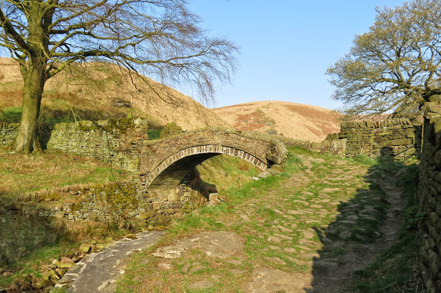 Where the stream splits, an ancient arched stone bridge carries the path over the water. In the background, moorland rises up.