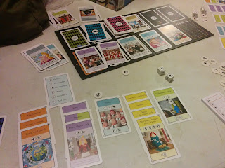 A game of CV in progress. The three decks are arranged at the top of the board, with one goal card beside them. Five cards are available to purchase along the bottom of the board. In the foreground, one player's tableau of purchased cards is visible. The special dice, can be seen, as well as the bonus tokens, scorepad, and a player aid.