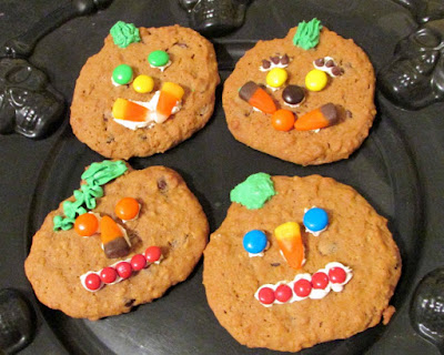 variety of candy faces on pumpkin cookies