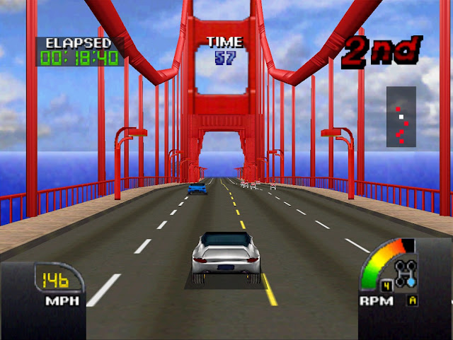 A silver car drives over the Golden Gate Bridge while racing.