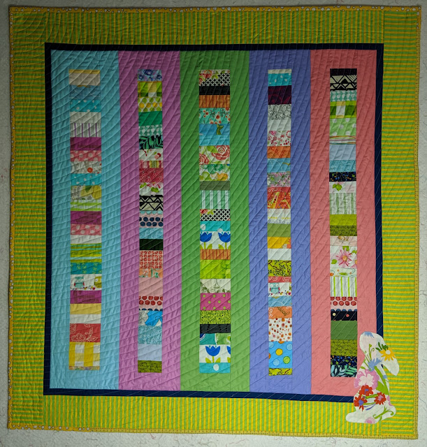 Narrow Chinese Coin columns are sashed with solid pastels. A narrow black border and a wide green and yellow striped border frame the quilt. The silhouette of a rabbit in a large floral print on white sits in the bottom right corner.