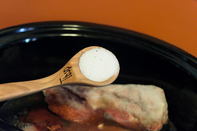 A measuring spoon with salt in it, over the slow cooker with the pork in it.