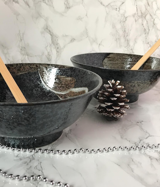 two black raman bowls with two wooden ladles