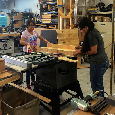 two students work at a tablesaw