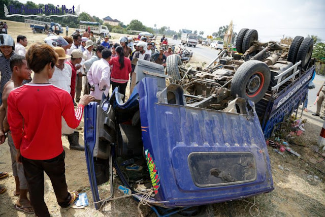 People inspect a truck at the scene of a fatal traffic accident in Kampong Speu province in January. Hong Menea
