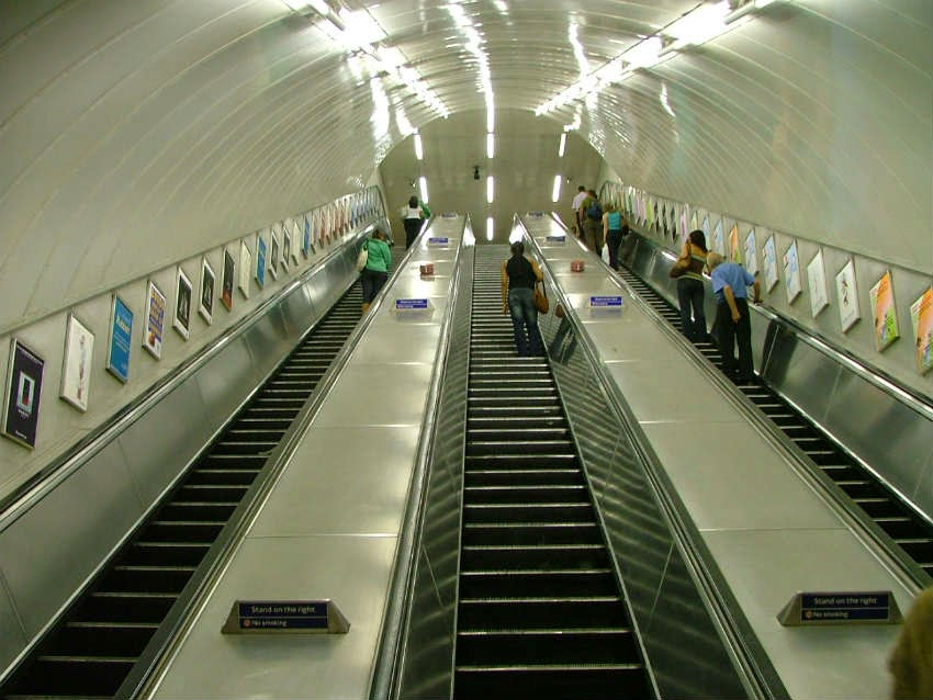 perspective from the bottom of the Tube escalators looking up, with eye level advertising either side.
