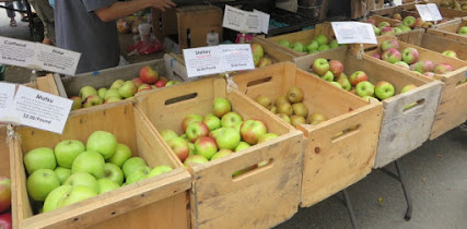 Wooden bins full of different kinds of apples