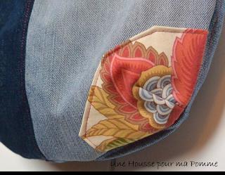 """Sac bandoulière fait de pans de pantalons en jeans recyclés (chinés par mes soins), de différents tons, montés façon patchwork, coutures surpiquées de fil rose, bandoulière en jeans, poche extérieure à rabat avec bouton et avec appliqué assorti, entièrement doublé en tissu coton au motif fleuri. Les jeans portés recyclés parfois délavés par le temps apportent cette """"petite chose en plus"""" à cette pièce unique. Dimensions : 35 x 33 x 8 cm, hauteur avec la bandoulière : 83 cm."""