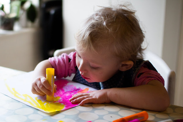 A toddler using paint sticks to create a valentine's day card