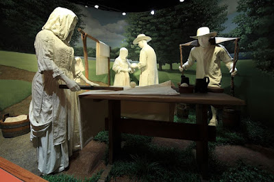 Four white-cast figures in museum exhibit arranged around a table with a drying rack behind. One man carries wooden buckets using a yoke across the back of his neck.