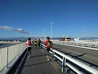 強風の橋の上を走るランナー