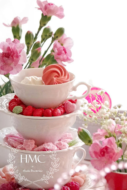 tea cups stacked and holding sweets centerpiece on tea table for valentines day