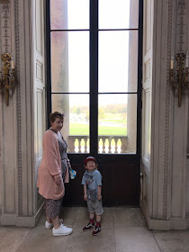 A mother and son standing in front of large double doors