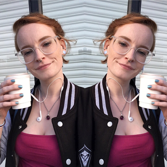 picture of myself (amy) wearing clear glasses from glasses shop and holding a take away coffee