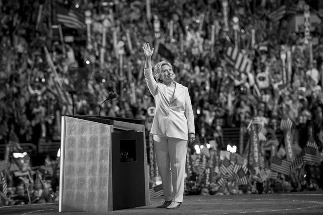 black and white image of Hillary Clinton standing onstage at the Democratic Convention, waving