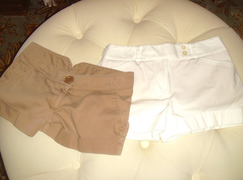 Two pairs of shorts on ottoman. One beige and one white.