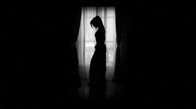 Woman in dress stands in profile of bright window in dark room. Dramatic.
