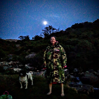 Moonlit scene on Dartmoor, a cheery woman (me) wrapped in a big coat after a river swim