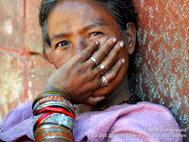 people, street portrait, headshot, face, eyes, Nepal, Kathmandu, beauty, Nepali lady, bangles, rings, eye contact, mouth guard gesture, dirty finger nails