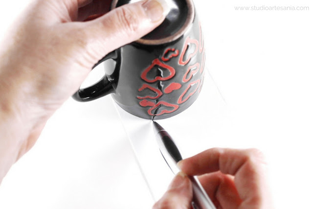 Photo of the hands drawing the template with the cup