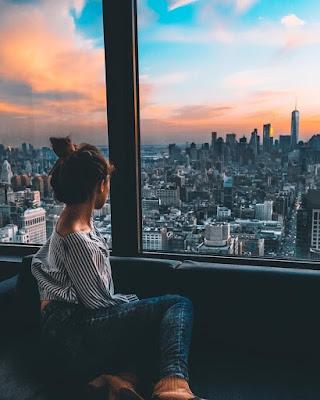 New York, une femme contemple les grattes ciels avec un couché de soleil