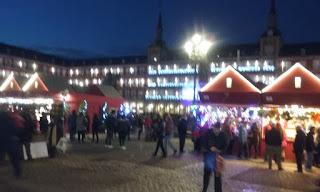 Panorámica de la plaza al atarcecer, con los casetas navideñas iluminadas y numerosos compradores frente a su mostradores.