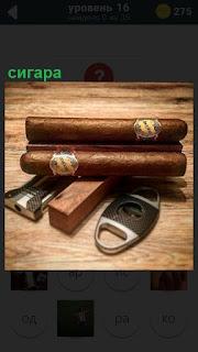 На крышке стола лежат сигары  с чехлом и ключ для откусывания кончика