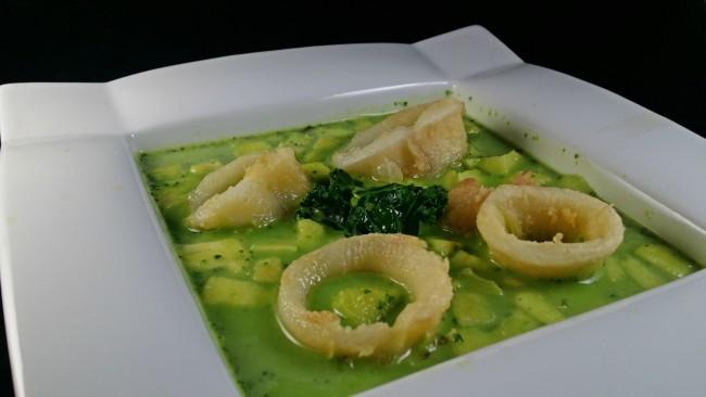 Una sopa de kale de color verde con calamares de adorno