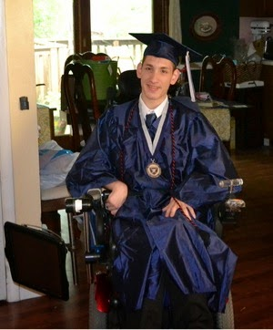 Bookshare member Zach Bryant, wearing college graduation cap and gown, seen sitting in a wheelchair.