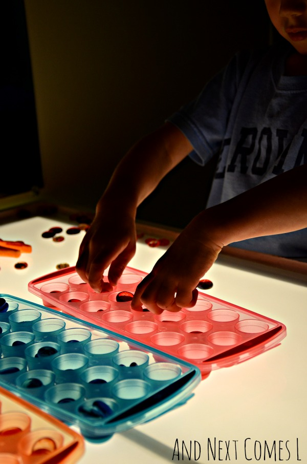 Light table activity using dollar store ice cube trays for fine motor practice from And Next Comes L