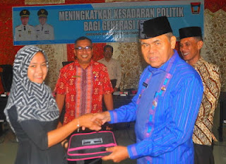Wakil Walikota Padang Emzalmi didampingi Kakan Kesbangpol, Eri Sendjaya menyerahkan bahan materi Sosialisasi Pendidikan Politik bagi Generasi Muda, kepada salah seorang peserta