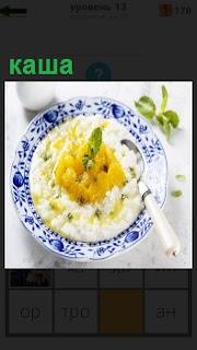 В тарелке приготовлена каша из риса на молоке и со сливочным маслом