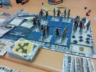 The game board in progress. The main game board has several human characters in the shelter, surrounded by a number of zombies.
