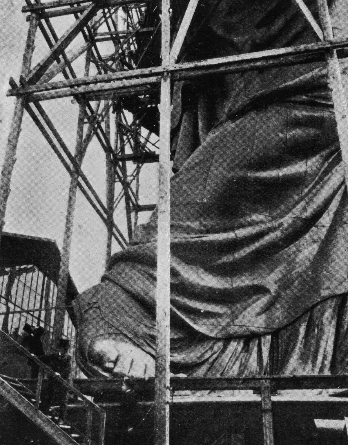 Tourists take a peek at Lady Liberty's massive foot as she is built in Paris before embarking on her long journey to the United States.