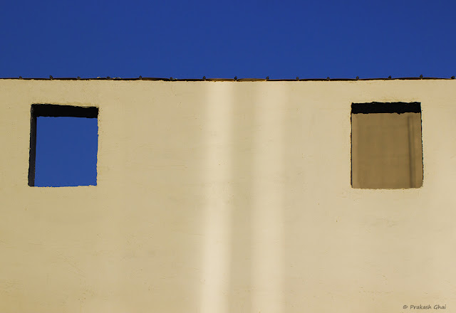 A Lookup Minimal Art Photograph of Two Windows on a Wall, one of which is open and the other one is closed.