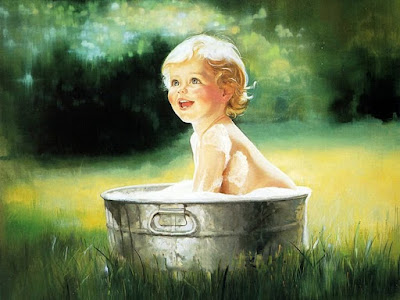A smiling young and beautiful child bathing in bowl on the grass, outdoors.
