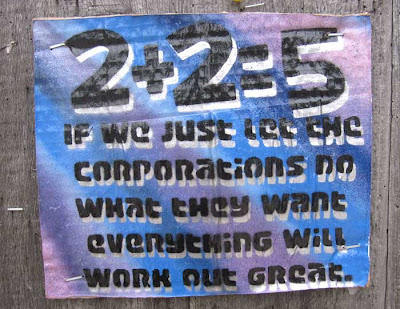 Corrugated cardboard sign, spraypainted purple and blue stripes, with black words 2+2=5 If we just let the corporations do what they want everything will work out great