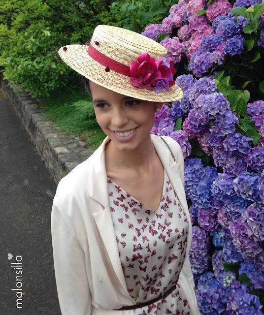 Look invitada con vestido de mariposas, chaqueta beig y canotier Luanco en burdeos, fondo de flores de hortensia