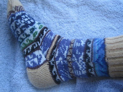 The colourwork sock being worn.  It now is flat and fits perfectly to the model's foot.