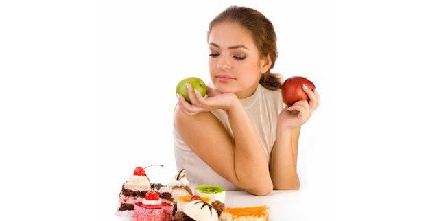 سيدة تحمل تفاحة حمراء وخضراء وامامها قطع كيك