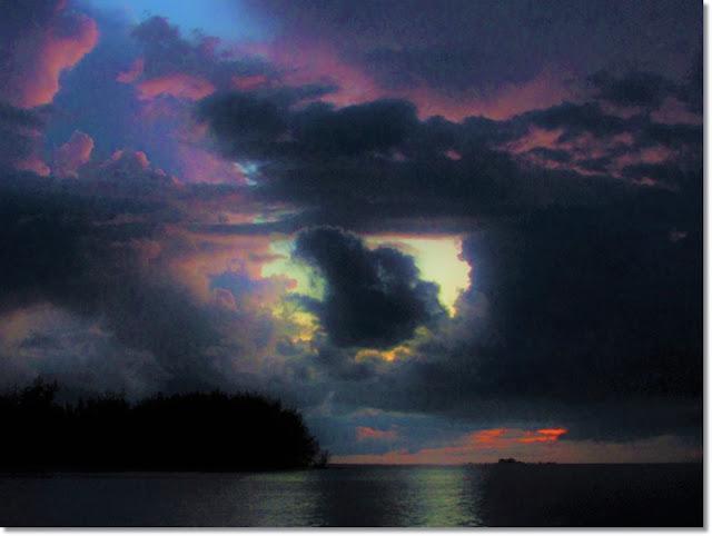 Bright sunset colors peak through ominous dark storm clouds over the ocean.