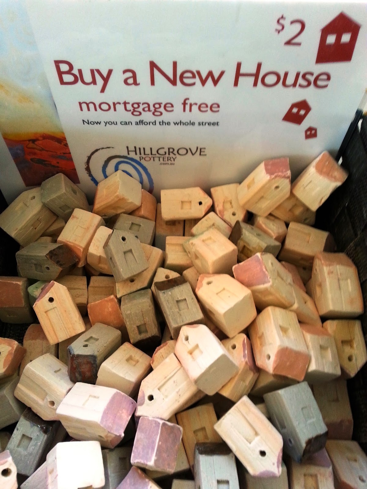 A large number of small clay houses, all jumbled together under a sign which says '$2 Buy a New House mortgage free'