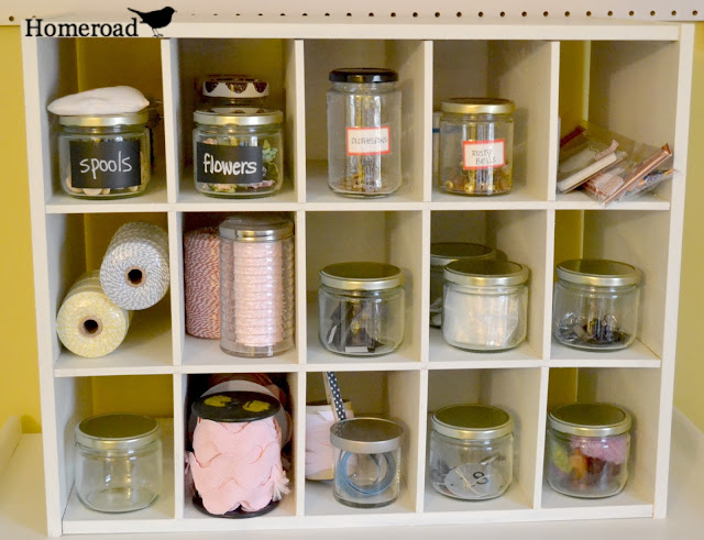 Multi space cubbie shelf with jars of crafts