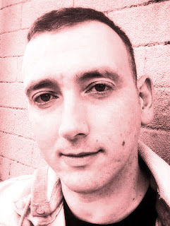 Casual close up author Cameron Macintosh, red-toned monochromatic image.