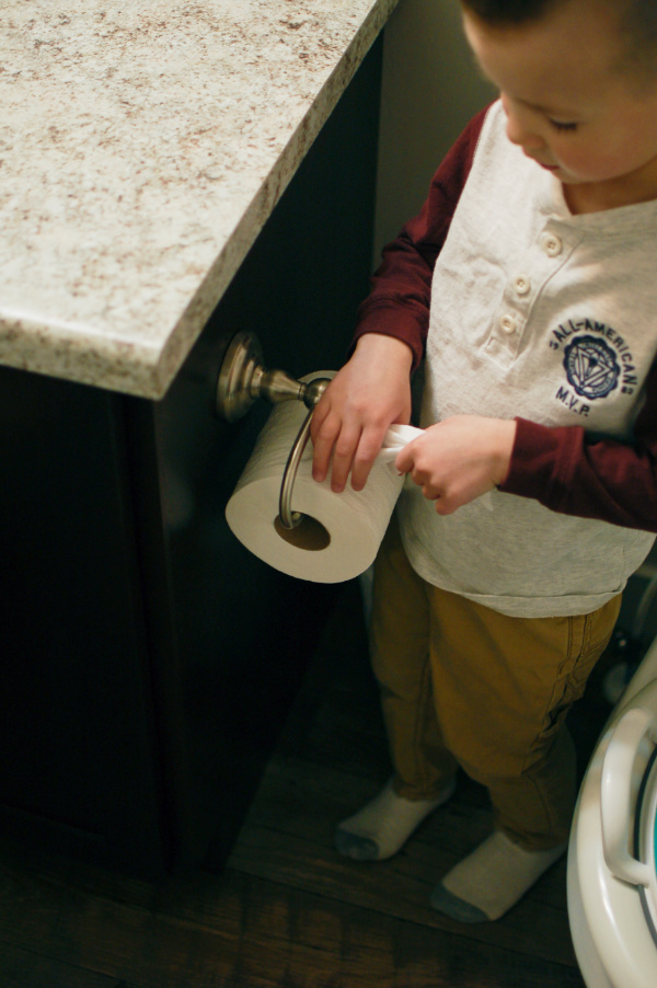 Little boy age 3 grabs some toilet paper and follows potty training advice.