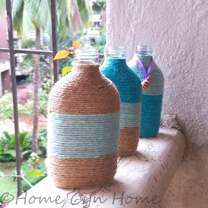 Embellish your twine wrapped bottles with seashells or pebbles for a coastal look.