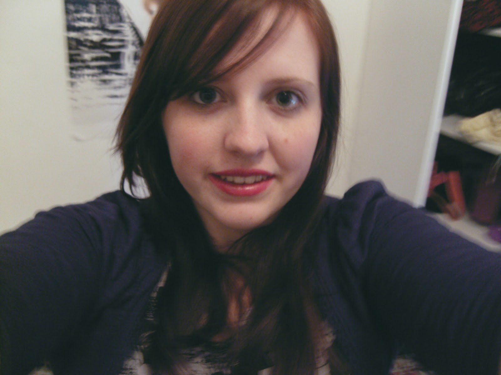 Photo of Sarah in 2008, aged 20. She has Brown hair that is past her shoulders and is wearing a grey t-shirt with blue cardigan