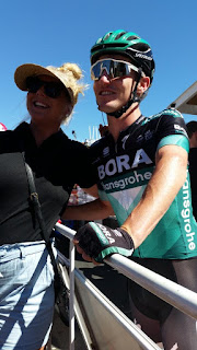 Jay McCarthy poses with the owner of the black Team Jay tee shirt. They have the race barrier fence between them. Jay is wearing his racing uniform including white rimmed sunglasses and the tee short owner is a woman with blonde hair in a ponytail, a sun visor and blue jeans. They each have one arm around each other and are smiling for the camera.