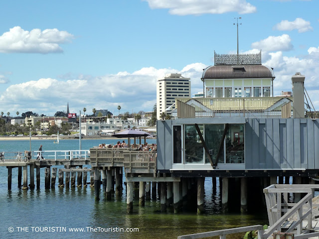 A Victorian house on stilts in the ocean with a town in the background.