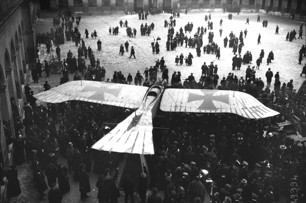 Photo of a captured German Taube monoplane, surrounded by a group of people, on display in the courtyard of Les Invalides in Paris, in 1915. Dogfights and other stories of pilots. marchmatron.com